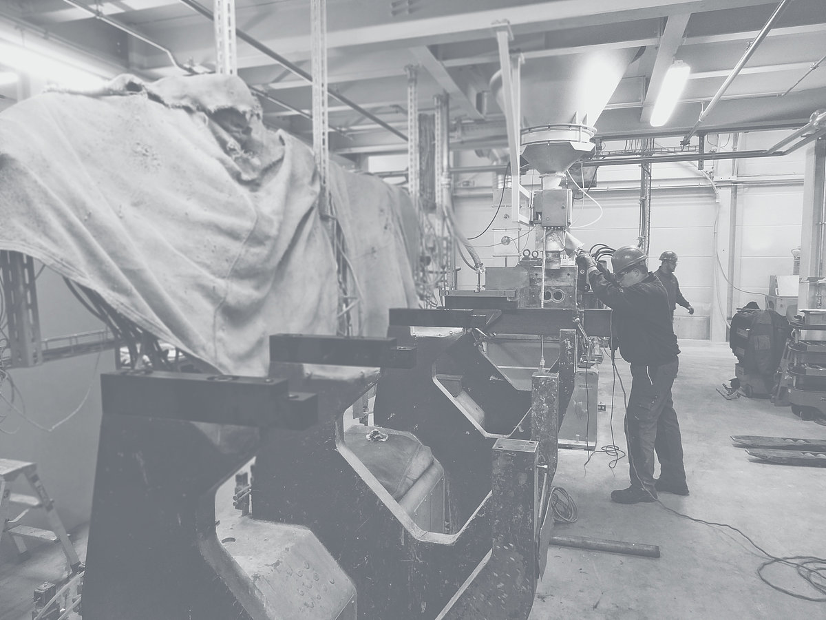Man operates a machine in a factory building