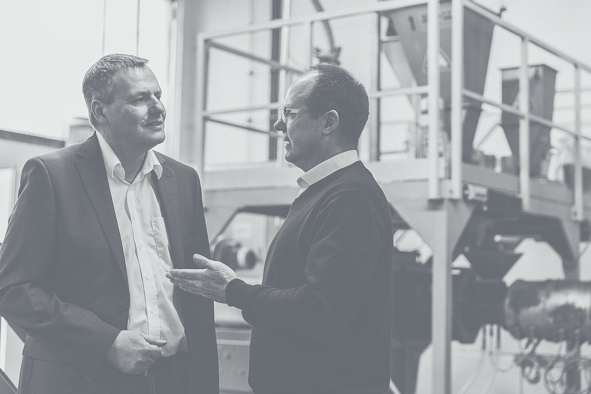 Sales Manager of Extruder Experts advises a customer in front of a machine