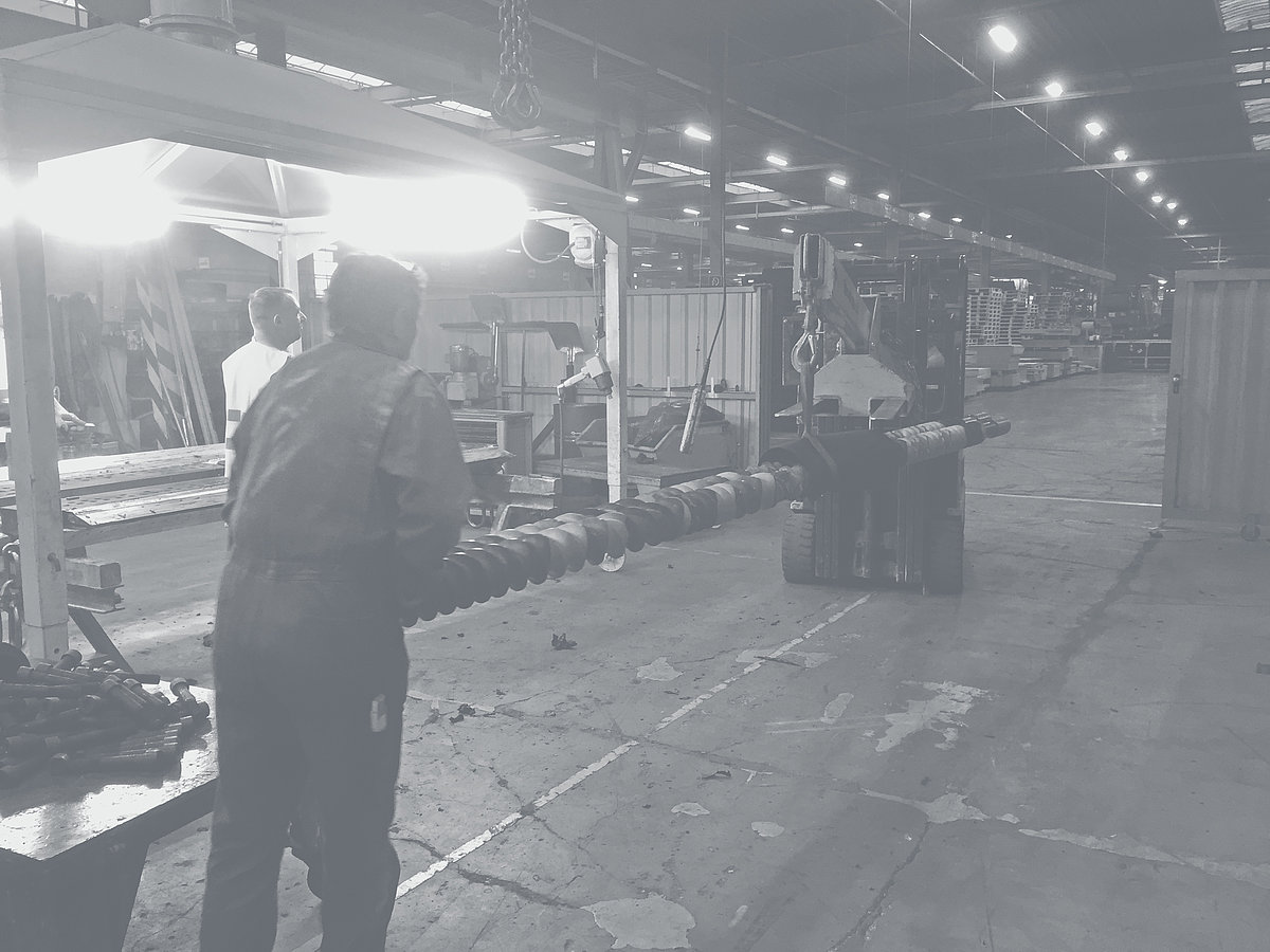 Forklift truck transports shafts with segments through a factory hall.